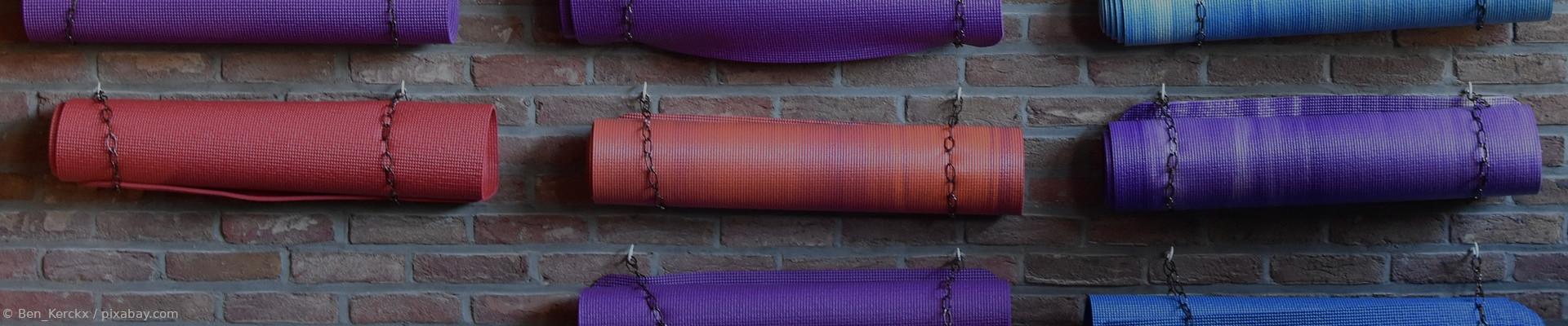 Viele Yogamatten an einer Wand